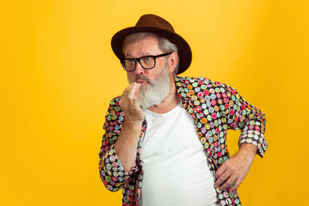 Sending kisses. Portrait of senior hipster man in eyewear isolated on yellow studio background. Tech and joyful elderly lifestyle concept. Trendy colors, forever youth. Copyspace for your ad.