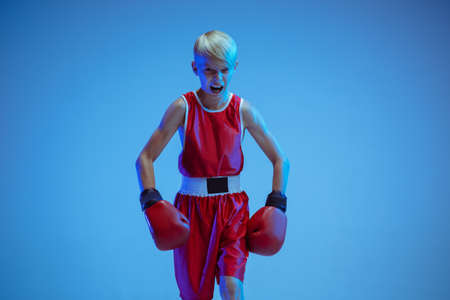 Teenager in sportswear boxing isolated on blue studio background in neon light. Novice male caucasian boxer training hard and working out, kicking. Sport, healthy lifestyle, movement concept. Stock Photo