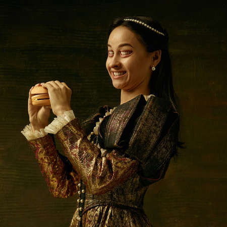 Medieval young woman in golden vintage clothing as a duchess posing on dark studio background. Concept of comparison of eras, modernity and renaissance. Surreal look with mouth instead eyes.