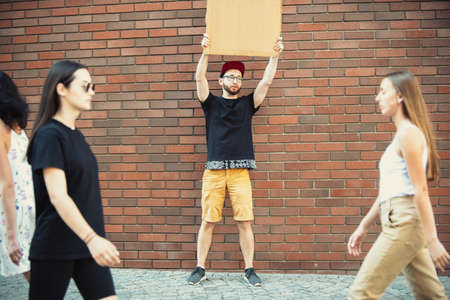 Dude with sign - man stands protesting things that annoy him. Solo demonstration his right to talk free on the street with sign. Copyspace for text. Opinion heard by public. Social life, humor, meme.