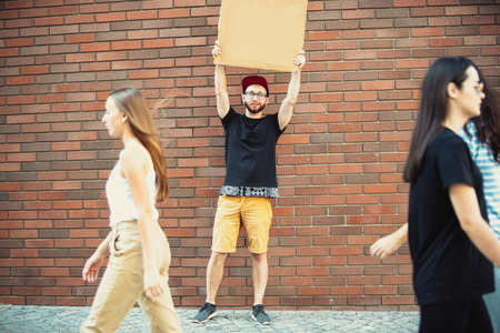 Dude with sign - man stands protesting things that annoy him. Solo demonstration his right to talk free on the street with sign. Copyspace for text. Opinion heard by public. Social life, humor, meme. Standard-Bild