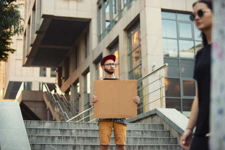 Dude with sign - man stands protesting things that annoy him. Solo demonstration his right to talk free on the street with sign. Copyspace for text. Opinion heard by public. Social life, humor, meme. Stock fotó