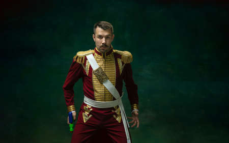 Tensioned duelist. Young man in suit as Nicholas II isolated on dark green background. Retro style, comparison of eras concept. Beautiful male model like historical character, monarch, old-fashioned.