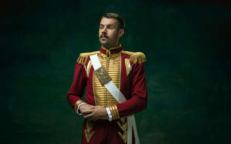 Highly serious. Young man in suit as Nicholas II isolated on dark green background. Retro style, comparison of eras concept. Beautiful male model like historical character, monarch, old-fashioned.