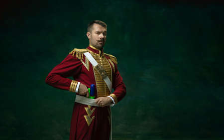 I have a gun. Young man in suit as Nicholas II isolated on dark green background. Retro style, comparison of eras concept. Beautiful male model like historical character, monarch, old-fashioned. Banque d'images