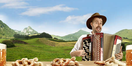 The happy smiling man with beer dressed in traditional Austrian or Bavarian costume holding mug of beer, mountains on background, flyer ready for ad. The celebration, oktoberfest, festival concept. Banque d'images