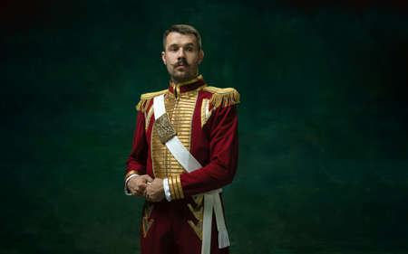Thoughtful. Young man in suit as Nicholas II isolated on dark green background. Retro style, comparison of eras concept. Beautiful male model like historical character, monarch, old-fashioned.