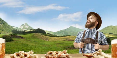 The happy smiling man with beer dressed in traditional Austrian or Bavarian costume holding mug of beer, mountains on background, flyer ready for ad. The celebration, oktoberfest, festival concept.