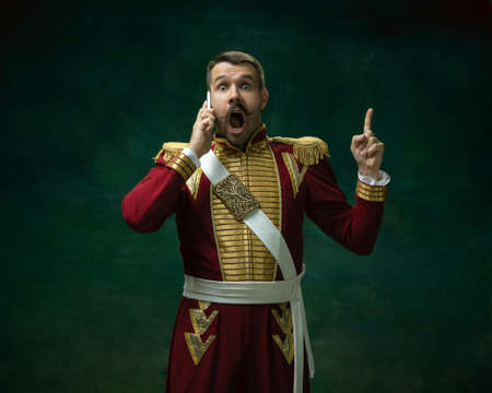 Talking phone. Young man in suit as Nicholas II isolated on dark green background. Retro style, comparison of eras concept. Beautiful male model like historical character, monarch, old-fashioned.