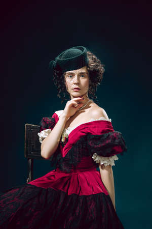 Love tragic. Young woman as Anna Karenina isolated on dark blue background. Retro style, comparison of eras concept. Beautiful female model like literature character, great, old-fashioned.