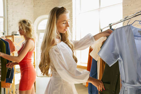 Wear, clothing shop during sales, summer or autumn collection. Young woman trying cloth, looking for new attire. Concept of fashion, style, offers, emotions, sales, purchases. Brand new shopping.