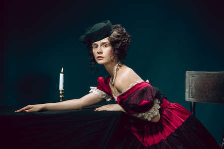 Sadness. Young woman as Anna Karenina isolated on dark blue background. Retro style, comparison of eras concept. Beautiful female model like literature character, great, old-fashioned.