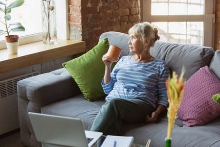 Listen to lector online. Senior woman studying at home, getting online courses, self-development. Caucasian woman using modern devices for having fun, education, spending time for new job or hobby.