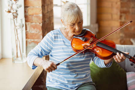 Learning to play violin online. Senior woman studying at home, getting online courses, self-development. Caucasian woman using modern devices for education, spending time for new job or hobby.