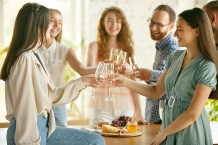 Team. People clinking glasses with wine or champagne. Happy cheerful friends celebrate holidays, meeting. Close up shot of smiling friends, lifestyle. Party at home or in restaurant, cafe.