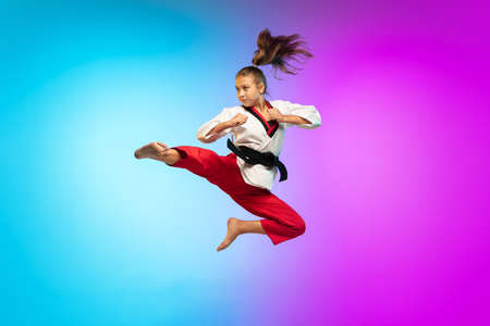 In jump. Karate, taekwondo girl with black belt isolated on gradient background in neon light. Little caucasian model, sport kid training in motion and action. Sport, movement, childhood concept.