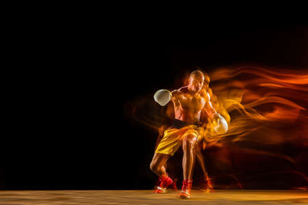 In fire. Professional boxer training isolated on black studio background in mixed light. Man in gloves practicing in kicking and punching. Healthy lifestyle, sport, workout, motion and action concept.