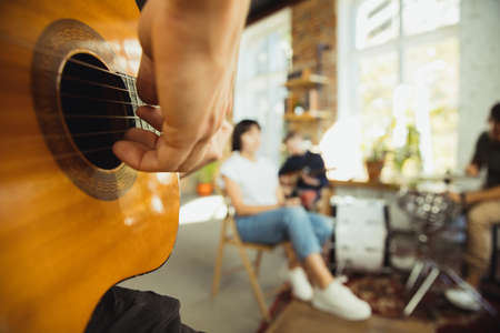 Close up hands playing. Musician band jamming together in art workplace with instruments. Caucasian men and women, musicians, playing and singing together. Concept of music, hobby, emotions, art occupation.