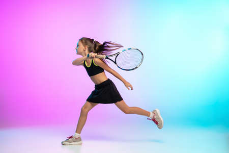 Unstoppable. Little tennis girl in black sportwear isolated on gradient background in neon light. Little caucasian model, sport kid training in motion and action. Sport, movement, childhood concept.