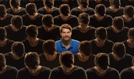 Top view of grey crowd of identical people and special one man, difference and diversity concept. Unique among the faceless, not like everyone else. Smiling and confident, feels happy. Collage. Standard-Bild