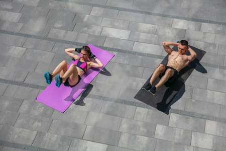 Young couple in sports outfit doing morning workout outdoors. Man and woman doing cardio and strenght exercises, practicing activity for lower and upper body. Sport, healthy lifestyle concept.
