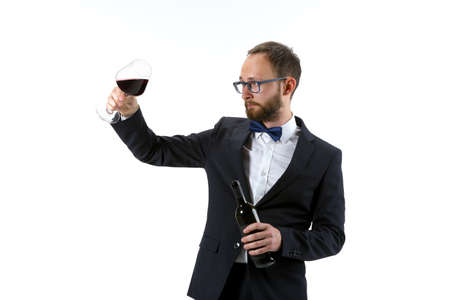 Trying red wine on. Portrait of male sommelier, wine steward or bar worker in white and black suit isolated over white background. Copyspace for ad. Concept of professional occupation, job.
