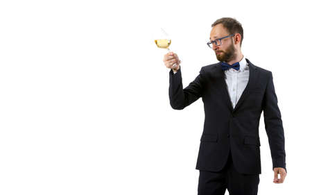 Trying white wine on. Portrait of male sommelier, wine steward or bar worker in white and black suit isolated over white background. Copyspace for ad. Concept of professional occupation, job.