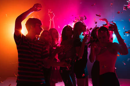 Wild. A crowd of people in silhouette raises their hands, dancing on dancefloor on neon light background. Night life, club, music, dance, motion, youth. Bright colors and moving girls and boys.
