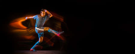 Win. Football or soccer player on black studio background in mixed light. Young male sportive model training in action. Kicking ball, attacking, catching. Concept of sport, competition. Flyer