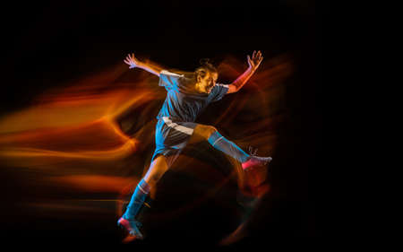 Motion. Football or soccer player on black studio background in mixed light. Young male sportive model training in action. Kicking ball, attacking, catching. Concept of sport, competition, winning.