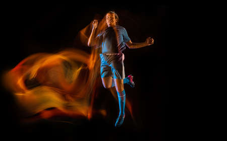 In fire. Football or soccer player on black studio background in mixed light. Young male sportive model training in action. Kicking ball, attacking, catching. Concept of sport, competition, winning.