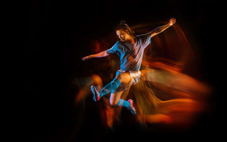 Jump high. Football or soccer player on black studio background in mixed light. Young male sportive model training in action. Kicking ball, attacking, catching. Concept of sport, competition, winning.