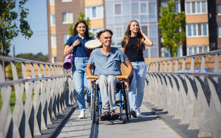 Emotions. Happy handicapped man on a wheelchair spending time with friends playing live instrumental music outdoors. Concept of social life, friendship, possibilities, inclusion, diversity.