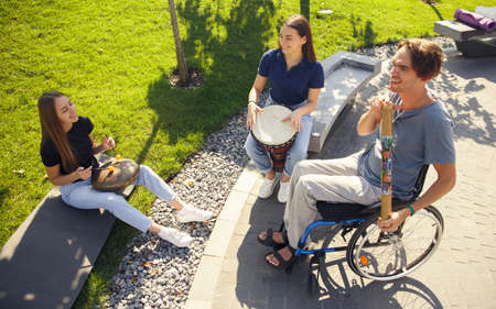 Full life. Happy handicapped man on a wheelchair spending time with friends playing live instrumental music outdoors. Concept of social life, friendship, possibilities, inclusion, diversity.