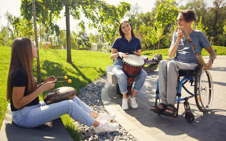 Happy handicapped man on a wheelchair spending time with friends playing live instrumental music outdoors. Concept of social life, friendship, possibilities, inclusion, diversity.