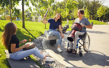 Hobby. Happy handicapped man on a wheelchair spending time with friends playing live instrumental music outdoors. Concept of social life, friendship, possibilities, inclusion, diversity. Foto de archivo