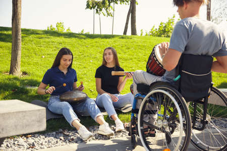 Inspiration. Happy caucasian handicapped man on a wheelchair spending time with friends playing live instrumental music outdoors. Concept of social life, friendship, possibilities, inclusion, diversity. Foto de archivo