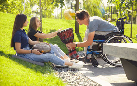 Inspiration. Happy caucasian handicapped man on a wheelchair spending time with friends playing live instrumental music outdoors. Concept of social life, friendship, possibilities, inclusion, diversity.