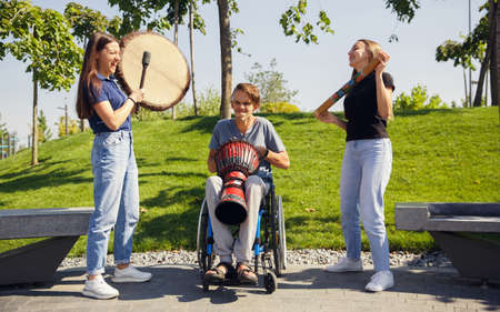 Aspiration. Happy caucasian handicapped man on a wheelchair spending time with friends playing live instrumental music outdoors. Concept of social life, friendship, possibilities, inclusion, diversity.
