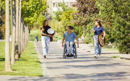 Summer. Happy caucasian handicapped man on a wheelchair spending time with friends playing live instrumental music outdoors. Concept of social life, friendship, possibilities, inclusion, diversity.