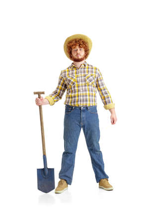 Handsome farmer, rancher isolated over white studio background. Concept of professional occupation, work, job, organic food. Copyspace for ad, text. Caucasian man with equipment for working. Stockfoto