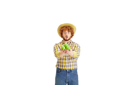 Handsome farmer, rancher isolated over white studio background. Concept of professional occupation, work, job, organic food. Copyspace for ad, text. Caucasian man with proposing apples.