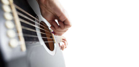 Close up of guitarist hand playing guitar, macro shot. Concept of advertising, hobby, music, festival, entertainment. Person improvising inspired. Copyspace to insert image or text.