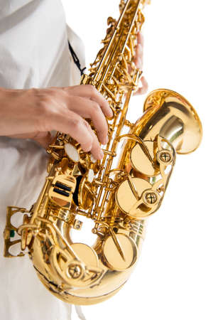 Close up woman playing saxophone isolated on white studio background. Inspired musician, details of art occupation, world classic instrument for jazz and blues. Concept of hobby, creativity.