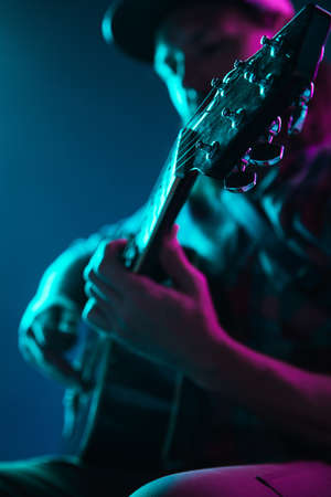 Close up of guitarist hand playing guitar, macro. Concept of advertising, hobby, music, festival, entertainment. Person improvising inspired. Copyspace to insert image or text. Colorful neon lighted. Stock Photo