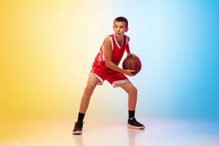 Strategy. Full length portrait of young basketball player in uniform on gradient studio background. Teenager confident posing with ball. Concept of sport, movement, healthy lifestyle, ad, action, motion.