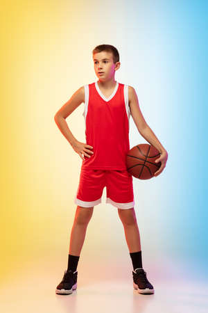 Full length portrait of young basketball player in uniform on gradient studio background. Teenager confident posing with ball. Concept of sport, movement, healthy lifestyle, ad, action, motion.