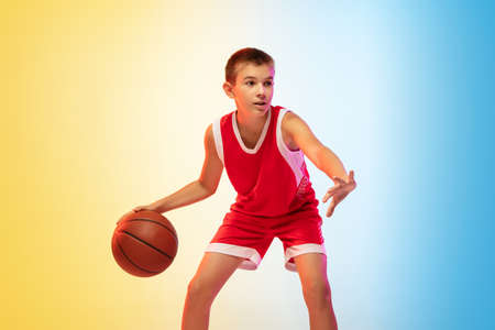 Full length portrait of young basketball player in uniform on gradient studio background. Teenager confident practicing with ball. Concept of sport, movement, healthy lifestyle, ad, action, motion. Stock Photo