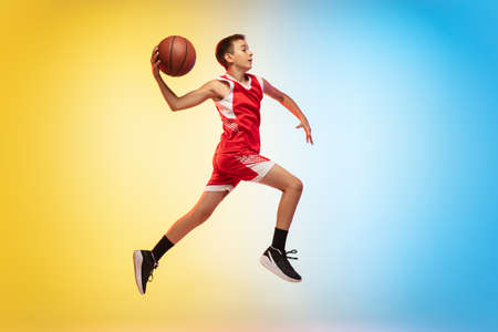 Jump high. Full length portrait of young basketball player in uniform on gradient studio background. Teenager confident posing with ball. Concept of sport, movement, healthy lifestyle, ad, action, motion.