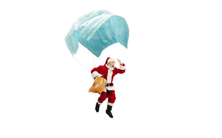 Santa Claus flying on huge face mask like on balloon isolated on white background. Caucasian male model in traditional costume. New Year, gifts, holidays, winter, COVID, pandemic concept. Copyspace. Archivio Fotografico